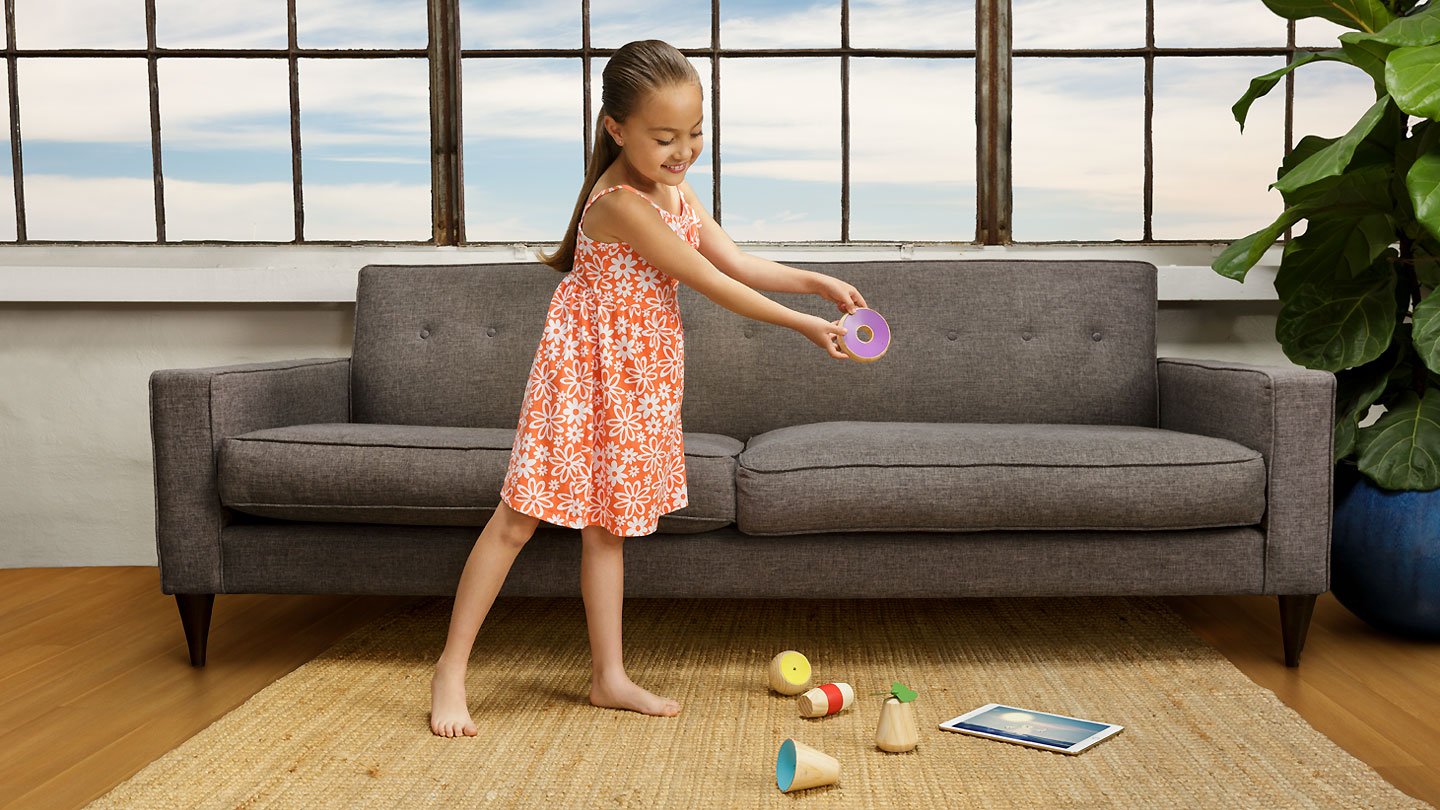 child playing with Yibu wooden toy connected with a game on tablet